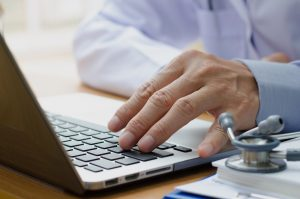 Close up of male doctor with laptop computer