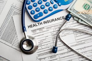Health insurance application form with money and stethoscope