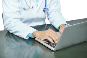 doctor typing on laptop telemedicine
